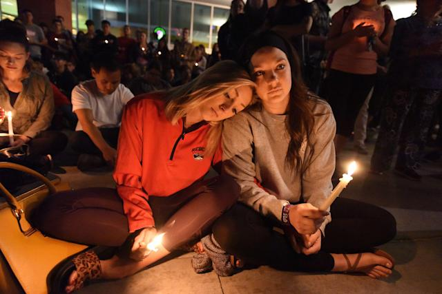 <p>Lindsay Cotterman (L) and Shawna Pieruschka attend a candlelight vigil at the University of Las Vegas student union October 2, 2017, after a gunman killed at least 58 people and wounded more than 500 others when he opened fire on a country music concert in Las Vegas, Nevada late October 1, 2017. (Photo: Robyn Beck/AFP/Getty Images) </p>