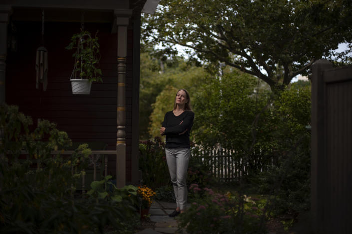 """Charlotte Breed Handy, 57, a direct descendant of a Pilgrim who came over on the Mayflower, stands for a portrait outside her home in Providence, R.I., Tuesday, Sept. 22, 2020. """"When I look back on my ancestry to the Mayflower, I do feel a little bit of ambivalence about it. But I also have a sense of pride about it from that side of my family, my dad's side. But I do feel like there's so much left out in terms of history when you follow a patriarchal line back. You're leaving out all the women that were pulled along the way,"""" said Breed Handy. """"I think that while it's good to take pride in your own culture and your own, whatever your feeling part of that, you're careful to respect other people's realities and cultures and way of being in the world, because there are a lot of different ways to be in the world."""" (AP Photo/David Goldman)"""
