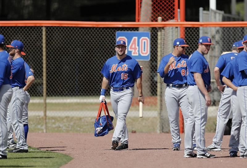 Former NFL quarterback and New York Mets outfielder Tim Tebow carries his equipment bag to a spring training baseball practice Monday, Feb. 27, 2017, in Port St. Lucie, Fla. (AP Photo/John Bazemore)