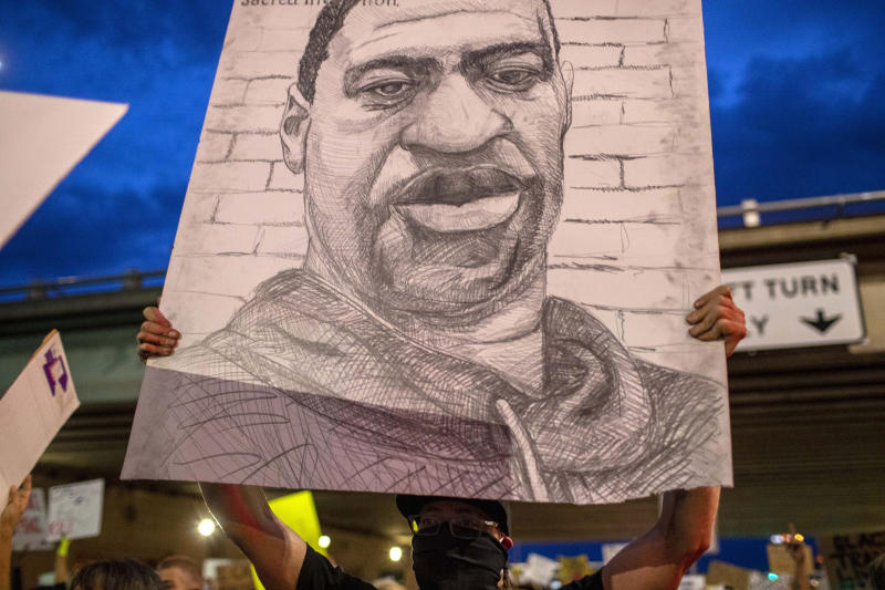 A demonstrator holds a drawing depicting George Floyd in Albuquerque, N.M., Sunday, May 31, 2020. Floyd was a black man who died in police custody in Minneapolis on May 25. (AP Photo/Andres Leighton)