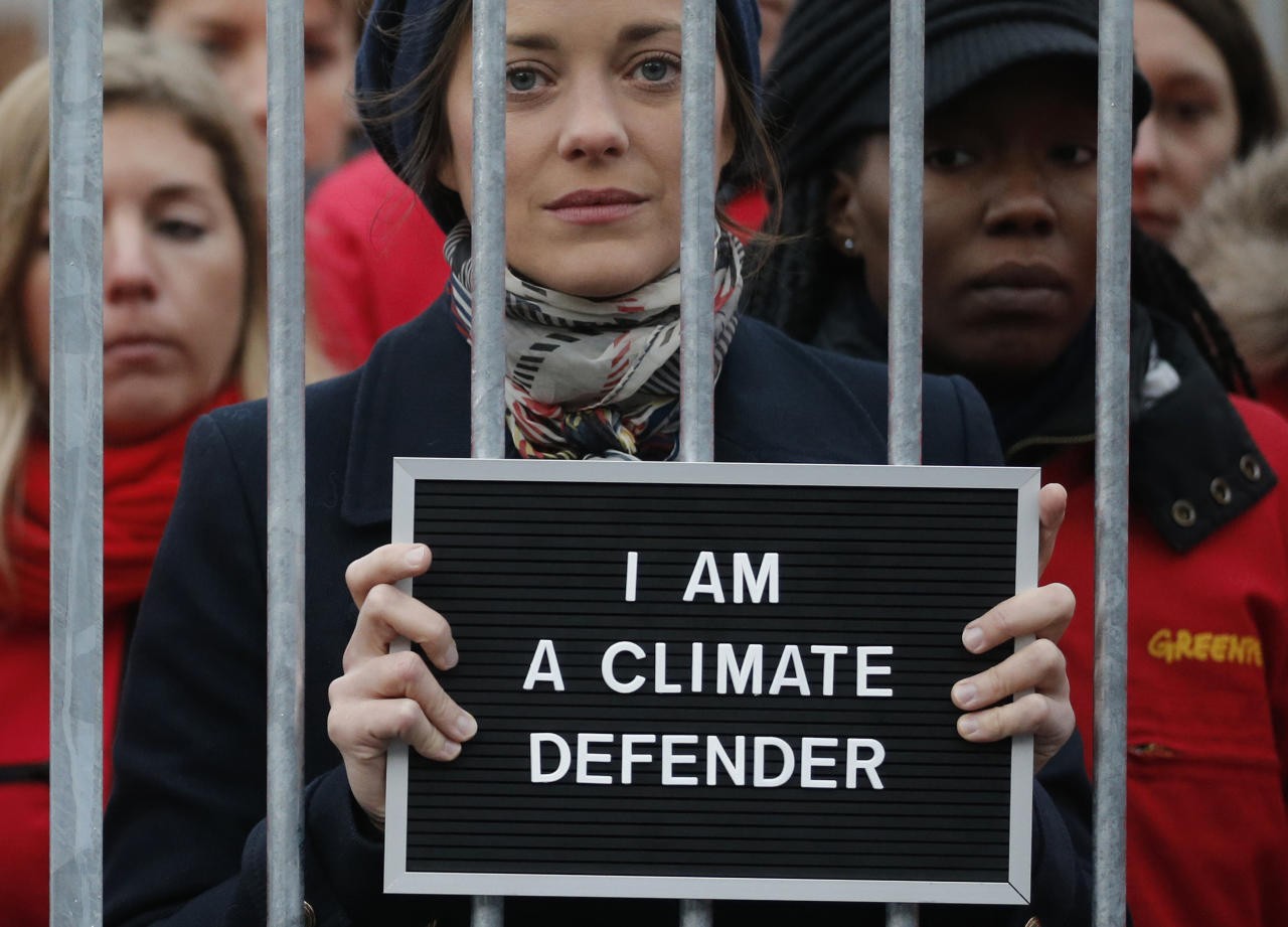 French actress Marion Cotillard (C) and Greenpeace activists protest inside a mock prison cell, in support of fellows activists who were detained on the boat Arctic Sunrise, during a protest action at Palais Royal place in Paris November 15, 2013. The group, consisting of 28 activists and two journalists, were arrested after coastguards boarded the Greenpeace icebreaker Arctic Sunrise following the protest at an oil platform owned by state-controlled Gazprom off Russia's northern coast on September 18.  REUTERS/Christian Hartmann  (FRANCE - Tags: POLITICS ENVIRONMENT CIVIL UNREST ENERGY ENTERTAINMENT TPX IMAGES OF THE DAY)