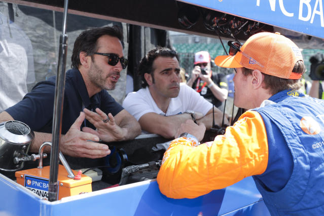 Scott Dixon, of New Zealand, talks with NASCAR driver Jimmy Johnson, left, and three-time Indy 500 champion Dario Franchitti, center, during practice for the Indianapolis 500 IndyCar auto race at Indianapolis Motor Speedway, Thursday, May 16, 2019 in Indianapolis. (AP Photo/Michael Conroy)