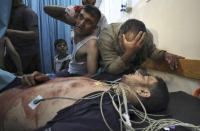 Mourners react in a hospital over the body of a man who died following an explosion in the town of Beit Lahiya, northern Gaza Strip, on Monday, May 10, 2021. (AP Photo/Mohammed Ali)