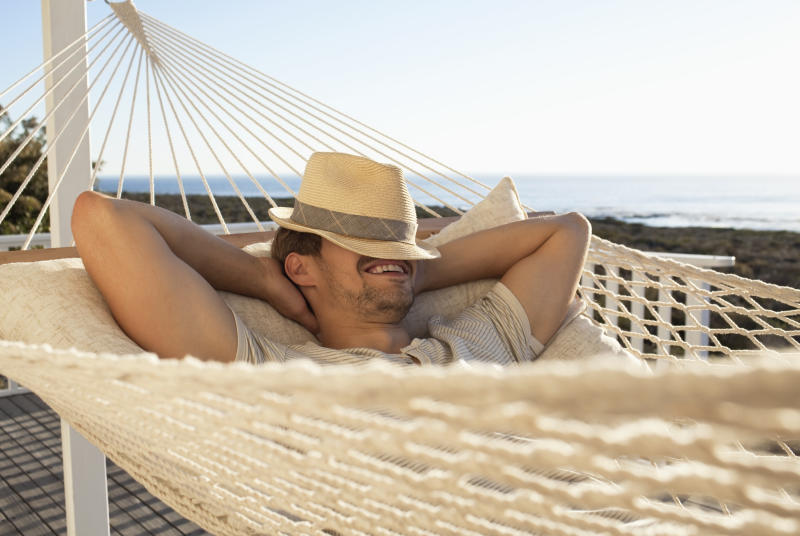 Cheerful young man smiling in hammock with his face covered by a hat