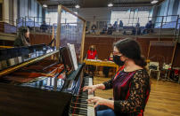 Ylenia Labanca, right, plays piano with a singer Yidan Fu, behind a transparent panel to curb the spread of COVID-19, during a lesson at the Giuseppe Verdi Music Conservatory, in Milan, Italy, Thursday, April 29, 2021. Whatever the instrument, flute, violin or drums, students at Italy's oldest and largest music conservatory have been playing behind plexiglass screens during much of the pandemic as the Conservatory found ways to preserve instruction throughout Italy's many rolling lockdowns. (AP Photo/Antonio Calanni)