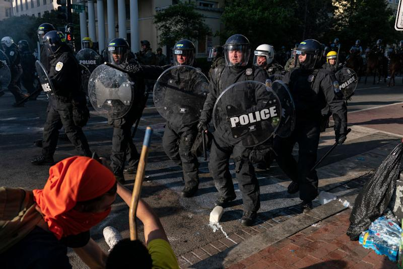 Pictured are police holding shields and pushing back protesters during a demonstration in Washington.