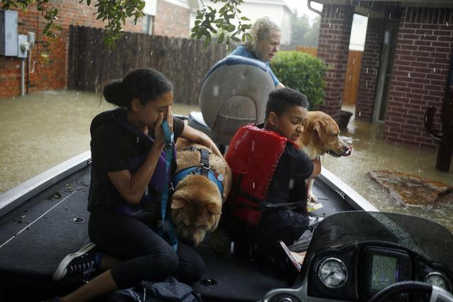 <p>A boy and girl hug their grandmothers' dogs after being rescued from rising floodwaters due to Hurricane Harvey in Spring, Texas, on Monday, Aug. 28, 2017. (Photo: Luke Sharrett/Bloomberg via Getty Images) </p>
