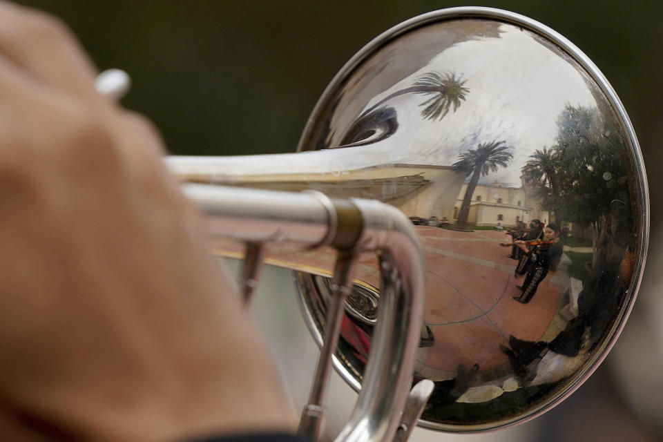 Memmbers of the Mariachi band Los Changuitos Feos (Ugly Little Monkeys) is reflected in the bell of a trumpet as they preform for parishioners in the courtyard of St. Augustine Cathedral Sunday, Aug. 18, 2021 in downtown Tucson. (AP Photo/Darryl Webb)