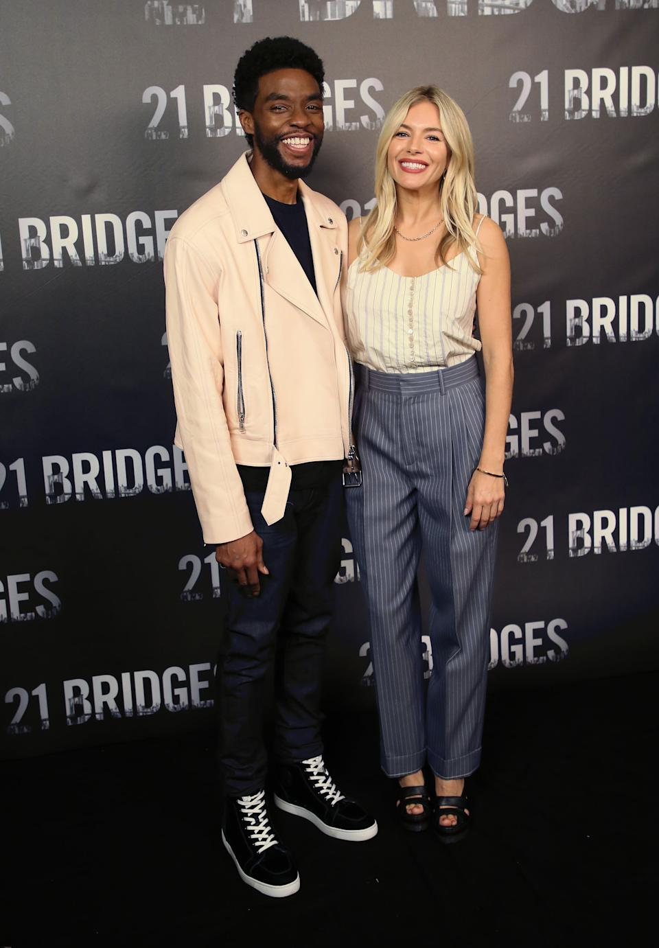 LOS ANGELES, CALIFORNIA - NOVEMBER 09: Chadwick Boseman and Sienna Miller attend a photocall for STX Entertainment's