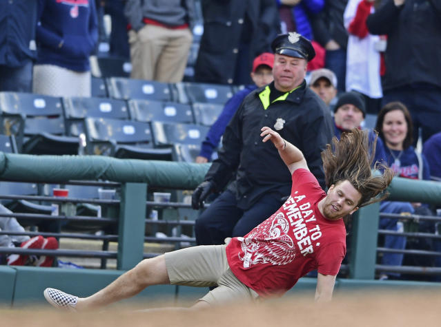 A fan slips and falls after running onto the field in the seventh inning of a baseball game between the Cleveland Indians and the Toronto Blue Jays, Saturday, April 6, 2019, in Cleveland. (AP Photo/David Dermer)