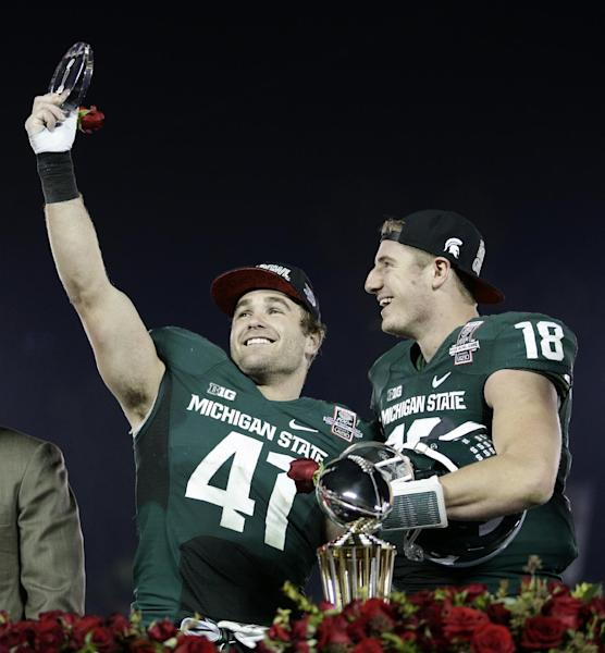 Michigan State linebacker Kyler Elsworth, left, celebrates with quarterback Connor Cook after Michigan State defeated Stanford 24-20 in the Rose Bowl NCAA college football game on Wednesday, Jan. 1, 2014, in Pasadena, Calif. (AP Photo/Jae C. Hong)