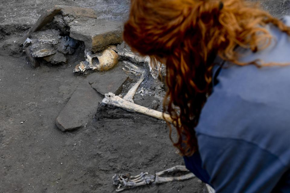 An archaeologist inspects skeletons in the Pompeii archaeological site, Italy(Ciro Fusco/ANSA via AP)