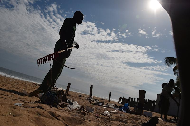 A man rakes up debris in the sand on a beach in Grand-Bassam on March 15, 2016, a day after a jihadist attack killed 19 people in the resort town (AFP Photo/Issouf Sanogo)