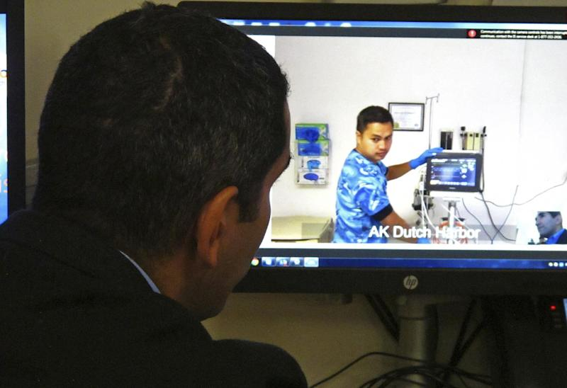 In this photo taken Sept. 13, 2016, critical care doctor Shadi Battah, left, in Anchorage, Alaska, converses with emergency medical technician Dmitri Dela Cruz at the Iliuliuk Family and Health Services on Unalaska Island during a demonstration of a new telemedicine partnership with Providence Alaska Medical Center. Beginning Thursday, Sept. 22, the Anchorage hospital will virtually beam critical care doctors 800 miles away to the emergency room of the clinic to assist staffers there during medical emergencies, thanks to a satellite link instead of the usual fiber optics. (AP Photo/Rachel D'Oro)