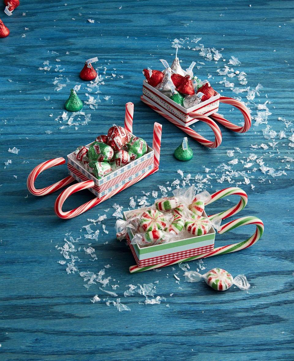 """<p>Everyone loves candy and when it comes delivered in a custom made candy cane sleigh it's even more special.<br><strong><br>To make:</strong> Wrap small white jewelry boxes in thin holiday<br>ribbon, holding it in place with double-sided tape. Attach two candy canes to the bottom of each box with hot-glue. Attach candy cane sticks (if desired) to the back of the box. Fill with candy.<br> <br><a class=""""link rapid-noclick-resp"""" href=""""https://www.amazon.com/Display-Guys-Cotton-Cardboard-Jewelry/dp/B07H11FRJH/ref=sr_1_2?tag=syn-yahoo-20&ascsubtag=%5Bartid%7C10050.g.645%5Bsrc%7Cyahoo-us"""" rel=""""nofollow noopener"""" target=""""_blank"""" data-ylk=""""slk:SHOP JEWELRY BOXES"""">SHOP JEWELRY BOXES</a></p>"""