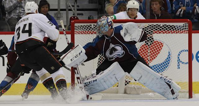 Colorado Avalanche goalie Semyon Varlamov, right, of Russia, deflects shot off the stick of Anaheim Ducks center Daniel Winnik in the third period of the Avalanche's 6-1 victory in a hockey game in Denver on Wednesday, Oct. 2, 2013. (AP Photo/David Zalubowski)