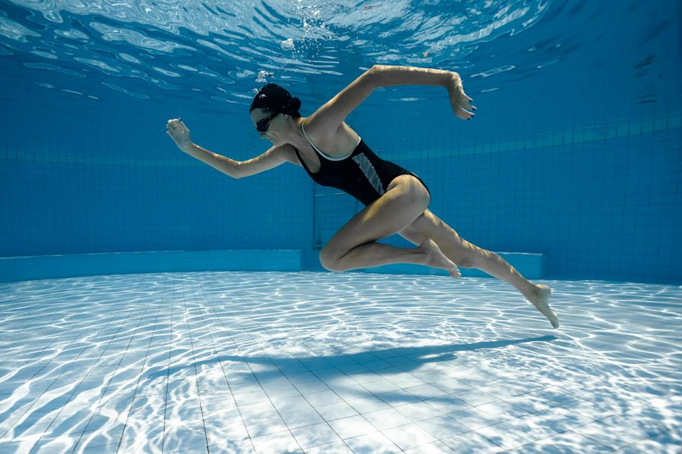 Woman's underwater run along the bottom of a swimming pool