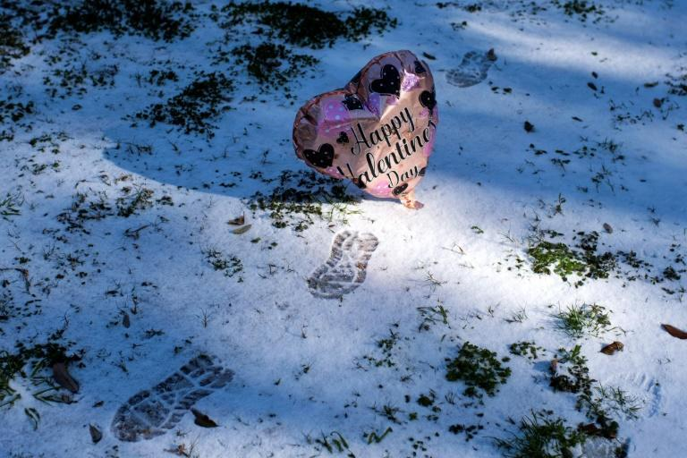 A Valentine's Day balloon floats past footprints in the snow in Houston, Texas on February 15, 2021