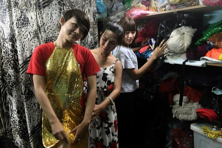 Huynh Nha An (R), 21, Jessica Nguyen (C), 31, and an unidentified trans person checking costumes inside Jessica's shop in Ho Chi Minh City