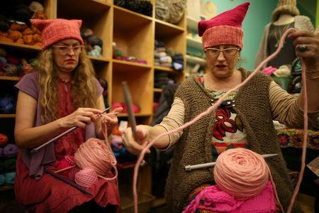 Molly Cleator (R) takes part in the Pussyhat social media campaign to provide pink hats for protesters in the women's march in Washington, D.C., the day after the presidential inauguration, in Los Angeles, California, U.S., January 13, 2017. REUTERS/Lucy Nicholson