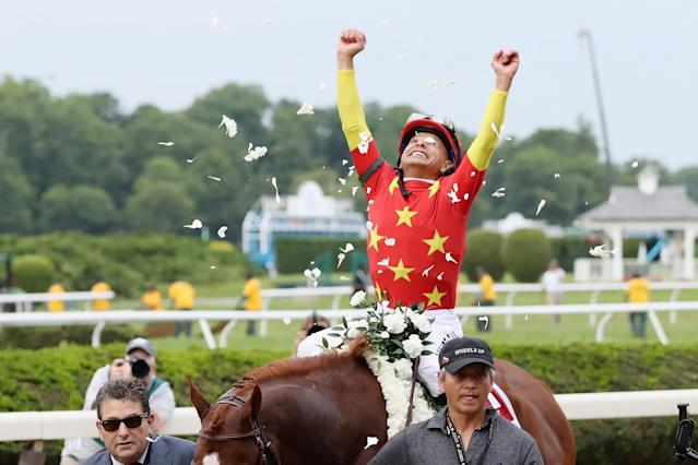 Mike Smith celebrates atop Justify after winning the Belmont Stakes and the Triple Crown. (Getty)