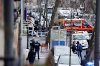 Police and firefighters gather at the site of a shooting in Montrouge, southern Paris