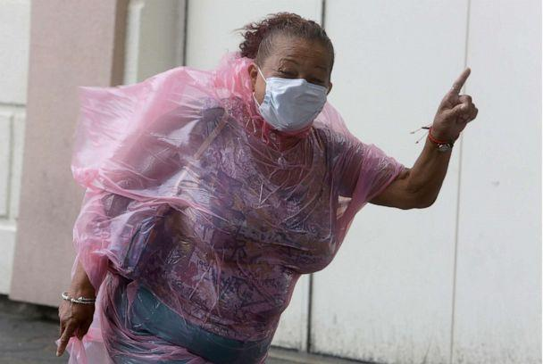 PHOTO: A woman shuts her eyes as she struggles to make her way into the Hard Rock Hotel & Casino during heavy winds, Aug. 4, 2020, in Atlantic City, N.J. (Jacqueline Larma/AP)
