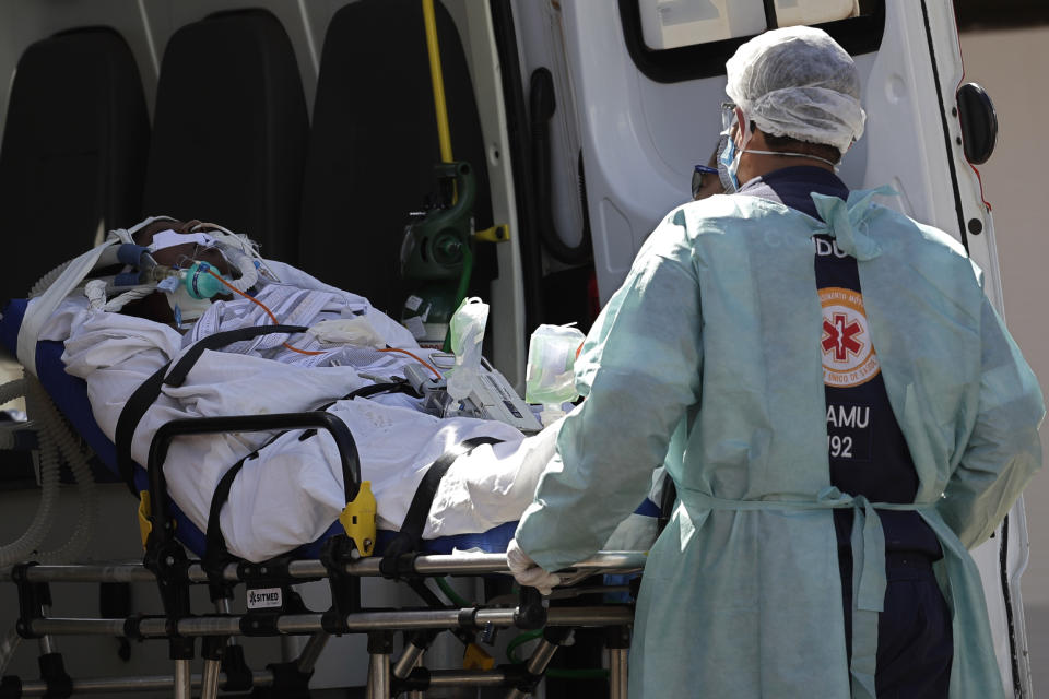 A patient suspected of having COVID-19 is received at the HRAN Hospital in Brasilia, Brazil, Wednesday, March 3, 2021.  The number of new COVID-19 cases in Brazil is still surging, with a new record high of deaths reported on Tuesday. (AP Photo/Eraldo Peres)