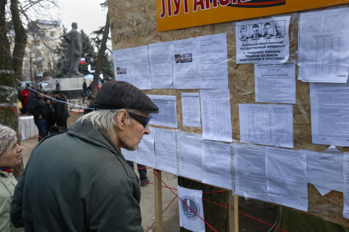 In this photo taken Tuesday, March 11, 2014, people read notices placed on an information board at a pro Russia camp set up in the town of Luhansk, eastern Ukraine, Tuesday, March 11, 2014. In 2010, the year of Ukraine's last presidential election, Luhansk gave 89% of its votes to Victor Yanukovych, a native of another town in the Donbas coal mining region. (AP Photo/Sergei Grits)