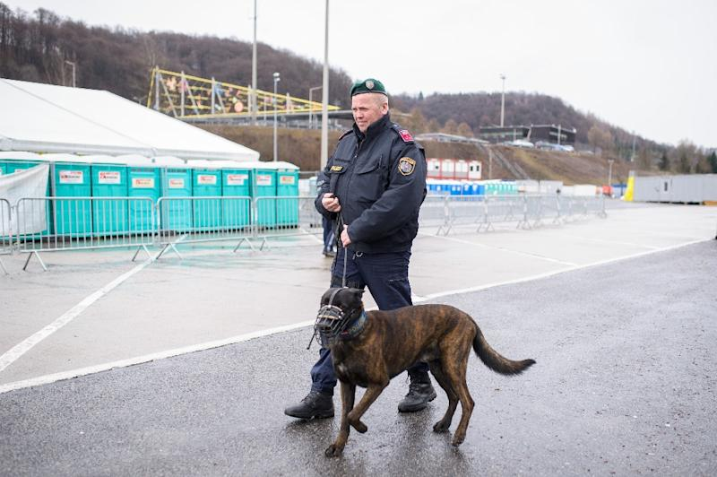 A police officer patrols with a dog at an empty refugee centre in Spielfeld at the Austrian-Slovenian border, as Austria imposes a new daily migrant limit on February 19, 2016 (AFP Photo/Rene Gomolj)