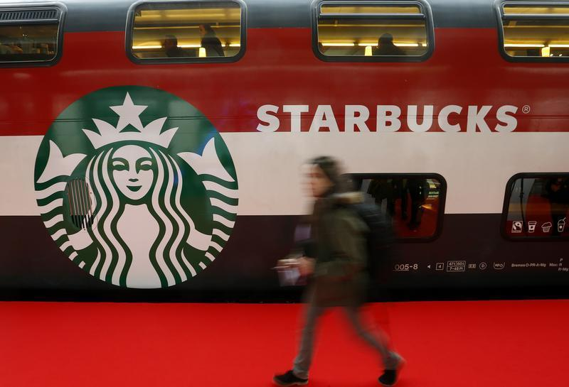 A woman walks past a Starbucks logo painted on a railway coach at the main train station in Zurich