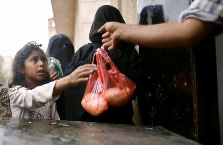 A girl receives a rice ration at a food distribution center in Sanaa, Yemen