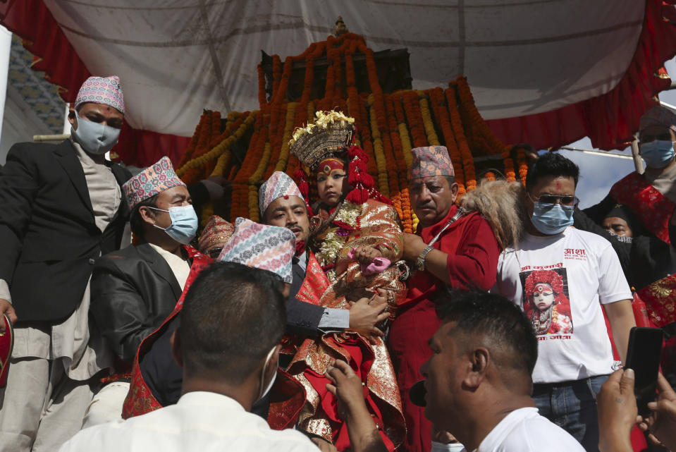 Nepal's revered living goddess Kumari is carried to be taken around in a wooden chariot during the annual Indra Jatra festival in Kathmandu, Nepal, Sunday, Sept. 19, 2021. The feast of Indra Jatra marks the return of the festival season in the Himalayan nation two years after it was scaled down because the pandemic. (AP Photo/Niranjan Shrestha)