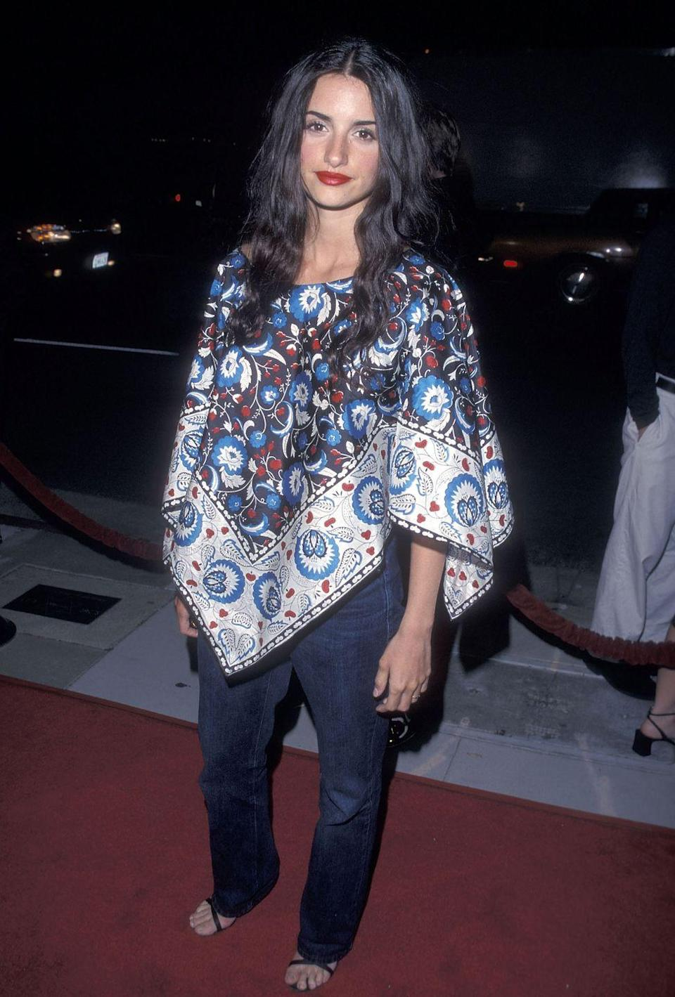 <p>Penelope wore a poncho (but a fancy silk one at that) to the premiere of <em>Cookie's Fortune</em> with dark-wash jeans, heels, and a red lip. Is it weird that I kind of want to wear one now? </p>