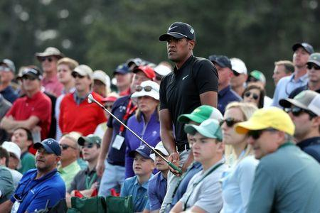 Tony Finau of the U.S. watches his chip shot to the 18th green from amid the crowd during first round play of the 2018 Masters golf tournament at the Augusta National Golf Club in Augusta, Georgia, U.S., April 5, 2018. REUTERS/Lucy Nicholson