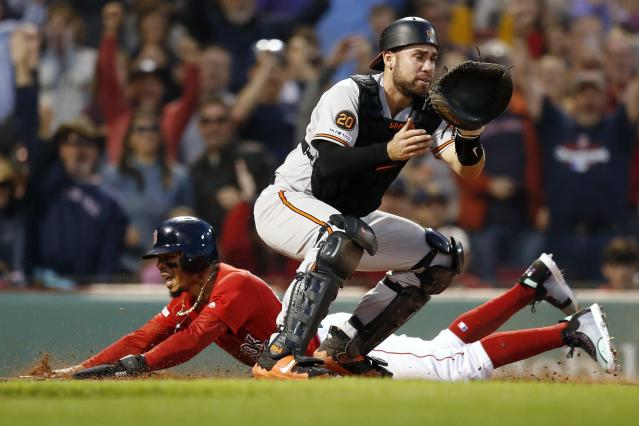 Boston Red Sox's Mookie Betts, left, scores the walk-off run on a single by Rafael Devers as Baltimore Orioles' Austin Wynns waits for the throw during the ninth inning of a baseball game in Boston, Sunday, Sept. 29, 2019. (AP Photo/Michael Dwyer)