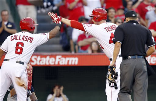 Los Angeles Angels' Alberto Callaspo (6) congratulates teammate Mark Trumbo, second from right, for hitting a solo home run in the fourth inning against the St. Louis Cardinals during a baseball game on Thursday, July 4, 2013, in Anaheim, Calif. Home plate umpire Adam Hamari, right, makes sure that Trumbo touches the plate. (AP Photo/Alex Gallardo)