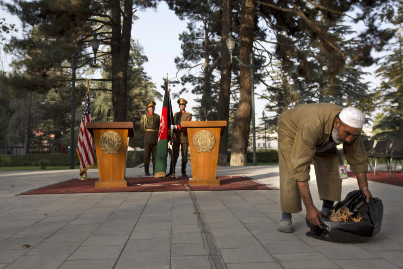 An employee of the Afghan Presidential Palace clears leaves from the site where U.S. Secretary of State John Kerry and Afghan President Hamid Karzai are expected to speak at a delayed news conference at the palace in Kabul, Afghanistan, on Saturday, Oct. 12, 2013, as a deadline approaches for a security deal about the future of U.S. troops in the country. Karzai and Kerry had a second meeting together at the Presidential Palace during Kerry's unannounced visit. The news conference was delayed for extended meetings between the Secretary and President. (AP Photo/Jacquelyn Martin, Pool)