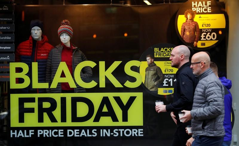 People walk past a sign advertising Black Friday offers in the window of a Blacks outdoor clothing store in Manchester, Britain