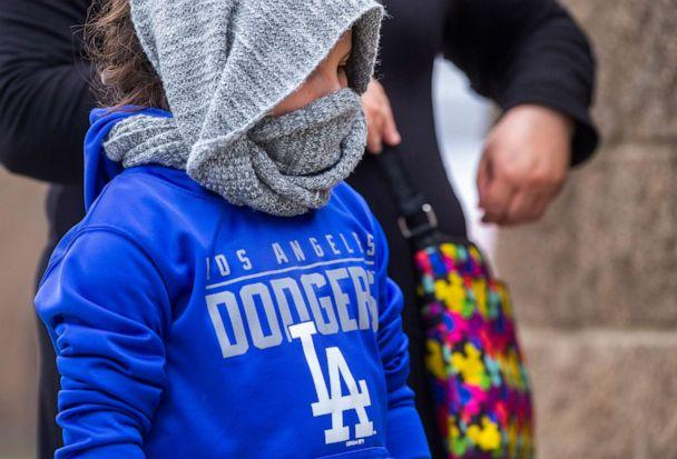 PHOTO: A little girl wears a scarf around her head as she lines up with her mother, looking to buy KN95 face masks outside Masataco, a taco shop in Whittier, Calif., Tuesday, April 7, 2020. (Damian Dovarganes/AP)
