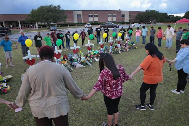 <p>Mourners pray around a memorial in front of Santa Fe High School on May 21, 2018 in Santa Fe, Texas. The makeshift memorial honors the victims of the May 18 shooting when 17-year-old student Dimitrios Pagourtzis entered the school with a shotgun and a pistol and opened fire, killing 10 people. (Photo: Scott Olson/Getty Images) </p>