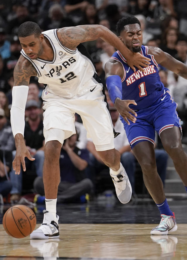 San Antonio Spurs' LaMarcus Aldridge (12) tangles with New York Knicks' Bobby Portis during the first half of an NBA basketball game Wednesday, Oct. 23, 2019, in San Antonio. (AP Photo/Darren Abate)