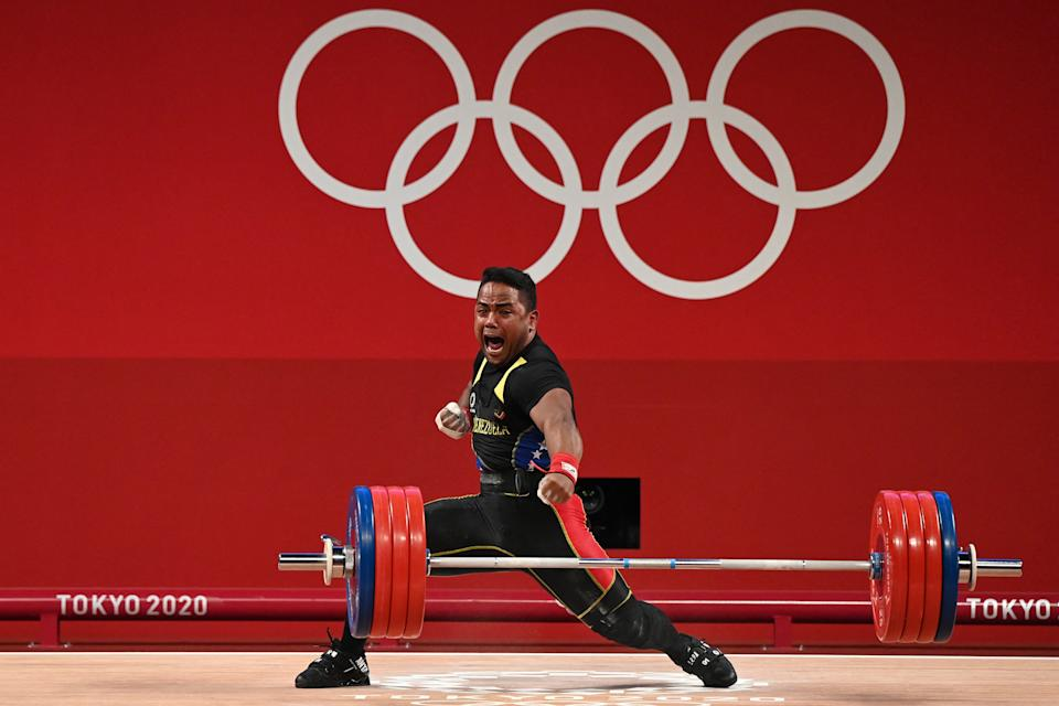 <p>Venezuela's Keydomar Giovanni Vallenilla Sanchez reacts after winning the silver medal in the men's 96kg weightlifting competition during the Tokyo 2020 Olympic Games at the Tokyo International Forum in Tokyo on July 31, 2021. (Photo by Luis ACOSTA / AFP) (Photo by LUIS ACOSTA/AFP via Getty Images)</p>
