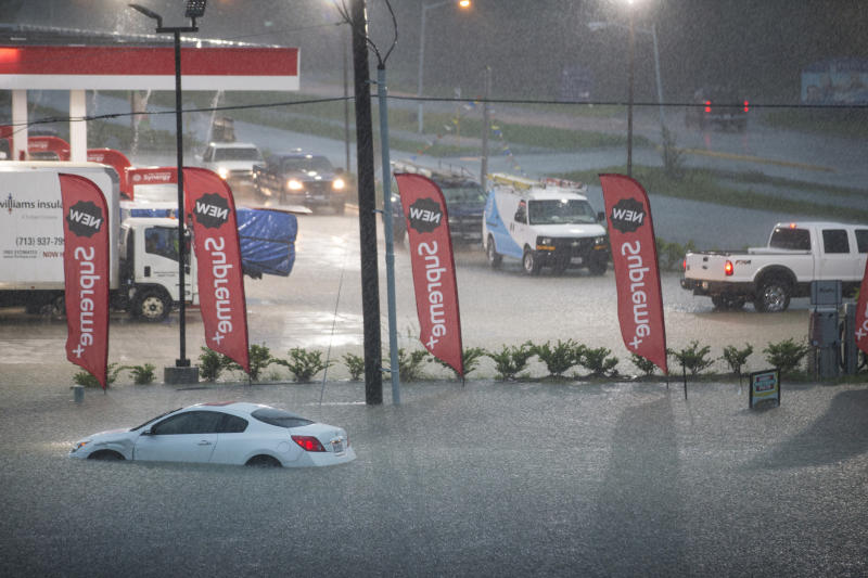 A flooded out car is stranded in high water off U.S. 59 as rain from Tropical Depression Imelda inundated the area on Thursday, Sept. 19, 2019, near Spendora, Texas. (Brett Coomer/Houston Chronicle via AP)