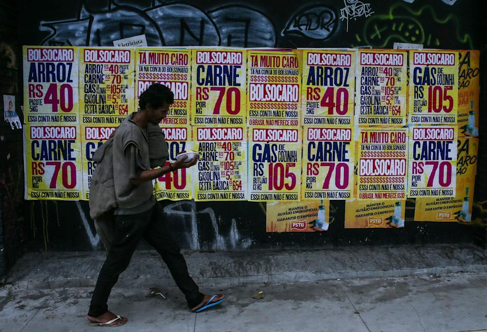 SAO PAULO, BRAZIL - MARCH 08: A homeless person walks in front of street posters depicting the price increases of basic items during the administration of Jair Bolsonaro and a slogan that reads