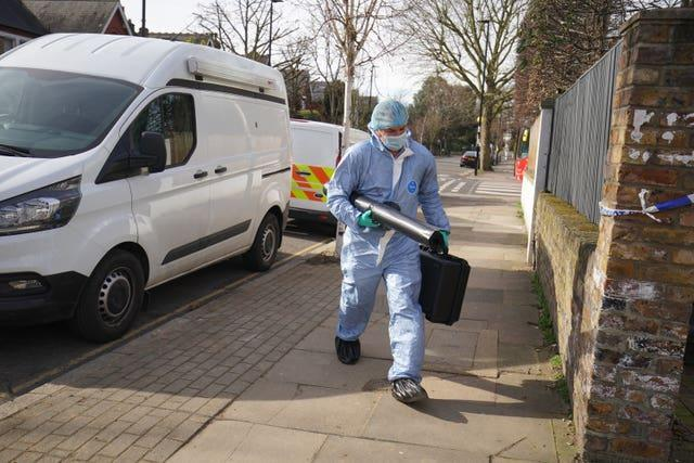 A forensic officer outside a property on Castlebar Road, Ealing, west London, where a woman in her 40s was found dead on Monday