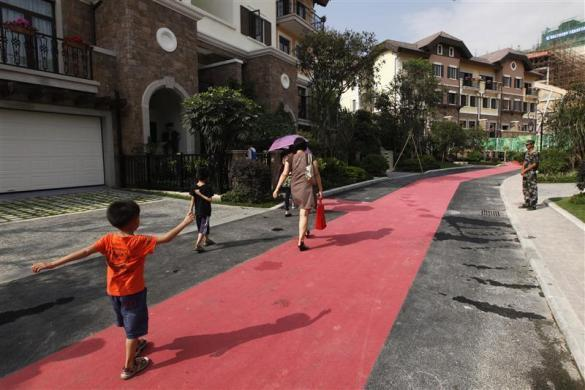 A family walks in front for are houses for sale at the replica village of Austria's UNESCO heritage site, Hallstatt, in China's southern city of Huizhou in Guangdong province, June 1, 2012.