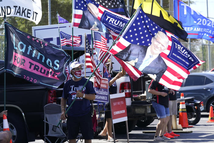 Orlando Bacallao carries a banner featuring President Donald Trump outside of an early voting location at the John F. Kennedy Library, Tuesday, Oct. 27, 2020, in Hialeah, Fla. (Lynne Sladky/AP)