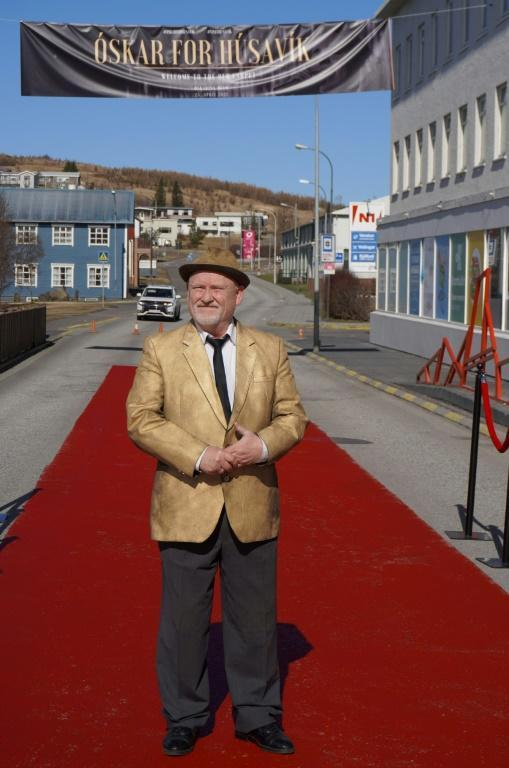 Icelandic actor Sigurdur Illugason posing on the main Husavik street painted in red, so residents can also experience the feeling of walking the red carpet