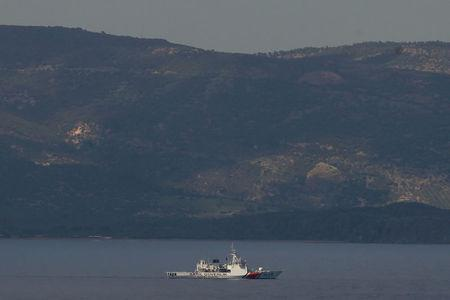 The Turkish shore is seen in the background as a Turkish coast guard vessel takes part in an operation after an inflatable boat carrying refugees and migrants sank and at least 15 people drowned, on the island of Lesbos